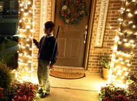 Zach Thibodeaux, 10, stares into the Christmas lights following his orientation and mobility training with specialist Rhonda Miller and father Adam Thibodeaux. The three ventured out for an evening of shopping at a center with Zach's blindfold and cane earlier this month. Zach, who has deteriorating eyesight due to cone-rod dystrophy, is teaching himself, with assistance, so he can eventually move about unassisted.