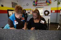 Selita Griffin, right, a resident staff member at Dallas LIFE Foundation, works at the homeless shelter's reception desk. She came to the shelter in June.(ROSE BACA)