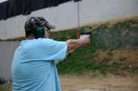 Dallas Pistol Club member Javier Criado shoots a round at the club's Carrollton range on Feb. 24, 2014. The private outdoor facility has been in the city of Carrollton since 1976, and the club has evolved since its early days.(Rose Baca - neighborsgo staff photographer)
