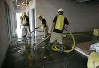 A crew worked Tuesday to remove water inside the new building for the Dallas Children's Advocacy Center, which is under construction in Far East Dallas. The break-in could delay the opening of the facility until December.