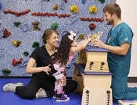 Four-year-old Melody Davis, who was born with spina bifida, is held steady by Allison Stavinoha as she works a puzzle held by Richard Stewart during a session with the physical therapists at Children's Medical Center Dallas.David Woo  -  Staff Photographer