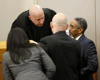 Attorneys huddle with state District Judge Brandon Birmingham in the murder trial of Delvecchio Patrick.