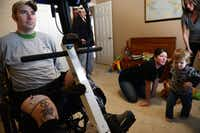 Colbert does therapy while his wife, Emily, and son, Deagan, play at their home. Colbert suffered a serious spinal cord injury in a car accident on Dec. 17, 2012. Doctors initially told him he would be paralyzed from the neck down, and since then he has regained use of his shoulders, arms and wrists, with limited function in his hands.(ROSE BACA)