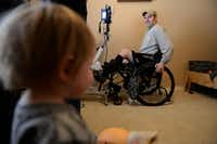 Garland firefighter Devon Colbert looks over at his son, Deagan, while he does therapy on a functional electrical stimulation bike at his home in Rockwall. Emily Colbert, Devon's wife, said life since the accident has become more routine for them and their two children, 2-year-old Levi and 17-month-old Deagan. But they said that stability wouldn't be possible without support from the community.(Photos by ROSE BACA)
