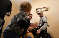 Colbert and his wife, Emily, share a smile with their son, Deagan, during therapy in their Rockwall home. An Austin-based website, The Chive, gave Devon a functional electrical stimulation bike and grant for therapy.ROSE BACA