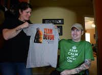 Garland firefighter Devon Colbert and his wife Emily, pictured in their home in Rockwall on Dec. 16, 2013, hold one of the t-shirt designs the Garland Fire Fighters Association is selling to benefit the couple. Colbert suffered a serious spinal cord injury in a car accident on Dec. 17, 2012. Doctors initially told him he would be paralyzed from the neck down, and since then he has regained use of his shoulders, arms and wrists, with limited function in his hands.( ROSE BACA )