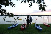 Lisa O'Connor and Steve Yauch prepare to kayak with the Dallas Downriver Club for a moonlight paddle at White Rock Lake in Dallas. The group, founded in 1975, has more than 85 members and is known for hosting the annual Trinity River Challenge in Carrollton and its Urban Saturday paddles on the Trinity River and White Rock Lake.(Rose Baca - neighborsgo staff photographer)