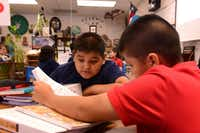 Fifth-grade students Jose Saavedra (left) and Ulisses Salto read an assignment in English at Brandenburg Elementary. Irving ISD's dual-language program is headed into its 10th year.