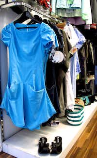 A blue dress made from hospital linens hangs above sandals constructed from recycled tire treads.