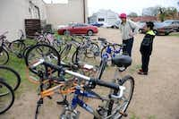 Francesca Funk, Earn-a-Bike event organizer, helps James look for a bike.(Rose Baca - neighborsgo staff photographer)