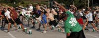 Berkner High School band director Frank Troyka (front, in green, back to camera) leads the ban through a 30-minute fitness routine before marching practice.