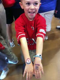 Slade Thompson of Dallas shows off his temporary Texas Rangers and Yu Darvish tattoos that he got at the Texas Rangers' Kids Zone.