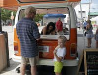Jason Runnels buys his daughter, Ellie Rose, an all-natural popsicle from Alicia Avila at the Pop Star Handcrafted Natural Popsicles stand during the opening of The Shed at the Dallas Farmers Market.Ron Baselice - Staff Photographer