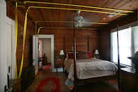 """ROOM AND BOARDS: Worley and Swenson's in-renovation bedroom, below, sans plaster but equipped with construction straps for straightening a leaning wall. The house's 1918 originality is what captivated Worley, although she did dig into its history at the Dallas Public Library before signing the deed in 2004. """"I wanted to make sure no ax murderers lived there,"""" she says. """"I didn't want any bad juju."""" The provenance checked out. Worley is the fourth owner in 94 years."""