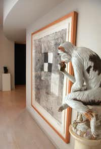 A giant Meissen monkey watches over the entry hall. The framed work on paper is I Ran A Muck No. 1, 1987, by William T. Wiley.