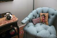 """In a corner of the main living space, a sweep of a tufted chair, by legendary English decorator Syrie Maugham. The two pillows in it? Betty Boop (a nod to Blake's nickname among friends) and, in French, """"The more I know men, the more I love my dog."""" The pitcher, at left, is by Pablo Picasso."""