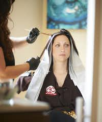 Tiffany Hicks having color applied to her hair.