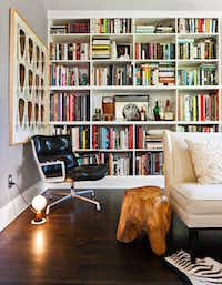 The living room's custom shelves hold books and a built-in bar. The Eames executive chair is from Herman Miller.