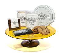 Hand-blown glass cake plate, $565, with 'Bite' brownie, $7; 'Dunk' cookies, canister $21; 'Munch' toffee, tin $45; and private-label dark chocolate bar, $6, Nest