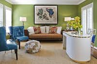 """""""I love having my own home office now,"""" says O'Neil, who reclaimed a guest bedroom during renovations. """"I've always been relegated to the kitchen table in the past."""" The new study beckons with avocado walls, a reupholstered day bed and peacock leather wingbacks and a fabric pouf from Mecox Gardens. The curvy desk from Again & Again was clad in """"little girl pink"""" grasscloth until the designers lacquered it white. Now Taylor says it's perfect in this """"big girl's room."""""""