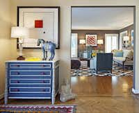 In the foyer, O'Neil's antique French bamboo-and-marble chest was amped-up with Chinese-red hardware and bright white trim on glossy slate lacquer.