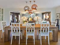 The designers wanted a rustic table in the dining room to balance the home's slick and pretty elements. They found it in a massive teak slab at Mecox Gardens, also the source for raw mango-wood chairs now painted gloss white and bronze. Seat cushions are an indoor-outdoor Trina Turk fabric that is easy to wipe clean. A trio of Globo Di Luce pendant lights in copper and silver are from Design Within Reach.