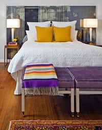 In the guest room, a Missoni throw is draped atop vintage metal ottomans upholstered in lavender velvet, a find from Blue Print on Fairmount St. The lamps are from Antiques Moderne. The designers fashioned the headboard from three French antique glass mirrors found at Again & Again.