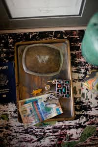 A vintage belt buckle and collectibles on Baker's bedside table