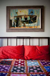 A vintage quilt and artwork add a pop of color to Baker's bedroom