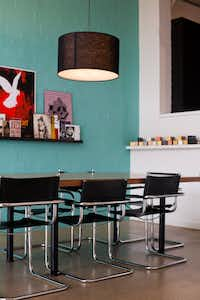 Black drum pendant lights and turquoise walls enliven a conference room.