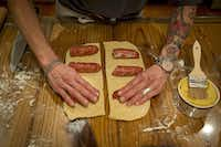 Katherine Clapner places sausages into cut pieces of dough as she makes kolaches at her home Friday, February 5, 2016 in Dallas.(G.J. McCarthy - Staff Photographer)