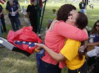 Patsy Maciel, right, the mother of Lance Cpl. Fred Maciel, who died in a helicopter in Iraq more than nine years ago, embraces Lanie Brown as she holds her son's flag at Calvary Hill Cemetery, Saturday, July 26, 2014, in Humble, Texas. Lanie and Walter Brown bought the flag for $5 after finding it tucked away in the corner of a flea market in Hemphill, about 170 miles from Houston. (AP Photo/Houston Chronicle, Karen Warren)(Karen Warren - AP)