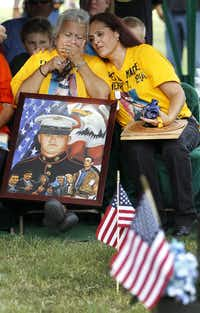 Hope Dorris, left, is comforted by her daughter, Patsy Maciel, the mother of Lance Cpl. Fred Maciel, who died in a helicopter crash in Iraq more than nine years ago, after being presented with a painting of him by Ken Pridgeon Sr. at Calvary Hill Cemetery, Saturday, July 26, 2014, in Humble, Texas. Later, Patsy was presented with a flag from Lanie and Walter Brown who bought the flag for $5 after finding it tucked away in the corner of a flea market in Hemphill, about 170 miles from Houston with messages by other marines about her son. (AP Photo/Houston Chronicle, Karen Warren)Karen Warren - AP