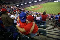Eugene Fletcher hugged Colin McClellan, 11, after the Rangers' Nelson Cruz homered against the Mariners in April.