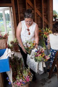 A Field to Vase dinner guest collecting her parting swag bag and fresh cut flowers.( California Cut Flower Commission  )