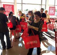 Customers check for gift cards in their free totes.