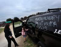 Kathy Casias (left), the Casiases' daughter-in-law, and her daughter get into their SUV that was painted with remembrances and tributes Wednesday after graveside services at Old Hall Cemetery in Lewisville.