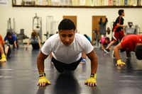 Anthony Belmares, 17, does pushups as part of the after-school boxing program at the Garland Police Boxing Gym. The program started 19 years ago as an initiative to reduce gang activity.(Rose Baca - neighborsgo staff photographer)