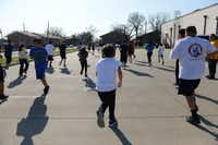 Kids run across the parking lot to warm up before the boxing program.(Rose Baca - neighborsgo staff photographer)