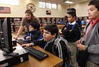 Sixth-grader Osvaldo Martinez (seated) searches through the list of books for Nook e-readers while visiting the media center with other friends at John F. Kennedy Middle School in Grand Prairie. At far right is sixth-grader Leonardo Lima.