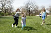 Alexis Dwyer, 8, chases Abby Kelley, 2, while Isabella Kelley, 9, watches the game of tag during a picnic in the Jonsson Color Garden at the Dallas Blooms floral festival, on Wednesday, March 19, 2014 at the Dallas Arboretum in Dallas.Ben Torres - Special Contributor