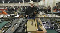 "FILE - In this Jan. 6, 2013 file photo, Ken Haiterman, of Pioneer Market, holds a CMMG 5.56mm AR 15 during the 2013 Rocky Mountain Gun Show in Sandy, Utah. A bipartisan quartet of senators, including two National Rifle Association members and two with ""F"" ratings from the potent firearms lobby, are quietly trying to reach compromise on expanding the requirement for gun-sale background checks."