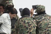 """Drug trafficker Joaquin """"El Chapo"""" Guzman is escorted to a helicopter by Mexican security forces at Mexico's International Airport in Mexico city, Mexico, on Saturday, Feb. 22, 2014. Mexico's apprehension of the world's most-wanted drug boss struck a blow to a cartel that local and U.S. authorities say swelled into a multinational empire, fueling killings around the world. Photographer: Susana Gonzalez/Bloomberg *** Local Caption *** Joaquin GuzmanSusana Gonzalez - Bloomberg"""