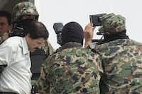 "Drug trafficker Joaquin ""El Chapo"" Guzman is escorted to a helicopter by Mexican security forces at Mexico's International Airport in Mexico city, Mexico, on Saturday, Feb. 22, 2014. Mexico's apprehension of the world's most-wanted drug boss struck a blow to a cartel that local and U.S. authorities say swelled into a multinational empire, fueling killings around the world. Photographer: Susana Gonzalez/Bloomberg *** Local Caption *** Joaquin Guzman(Susana Gonzalez - Bloomberg)"