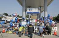 Mourners gather at a gas station in Houston on Saturday, Aug. 29, 2015 to pay their respects at a makeshift memorial for Harris County Sheriff's Deputy Darren Goforth who was shot and killed while filling his patrol car. On Saturday, prosecutors charged Shannon J. Miles with capital murder in the Friday shooting. (James Nielsen/Houston Chronicle via AP)