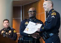 Dallas Police officer Matthew Smith, right, receives a commendation award from Dallas Police Chief David O. Brown on Thursday, July 2, 2015 at Dallas Police headquarters in Dallas. On June 14, 2015, a lone gunman in an armored vehicle fired on DPD headquarters, then led officers on a chase to Hutchins, Texas, where the gunman was surrounded and killed after an overnight stand-off. Major Andy Harvey, left, acted as emcee for the event. (Ashley Landis/The Dallas Morning News)