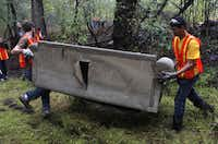 Volunteer Jay Orelup (left) helps Raul Leyva, a student from Williams Preparatory School carry a couch out of the Joppa Preserve.