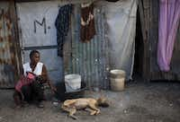 A woman sits with her daughter in front of her tent at a camp set up for people displaced by the 2010 earthquake in Port-au-Prince, Haiti, Monday, Dec. 10,  2012. Haiti's President Michel Martelly  says his government is building homes and creating jobs almost three years after a catastrophic earthquake. (AP Photo/Dieu Nalio Chery)