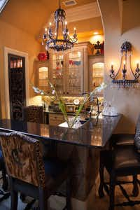 This home bar brings the bling, with monogrammed chair backs, lots of crystals on the light fixtures and decorative faux finished on the backsplash and beneath the bar.