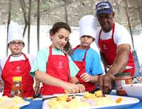 Dallas Cowboys legend Preston Pearson, right, assists children, Elliot Levy, 11, left, Jordan Levy, 11, and Miles Levy, 11 with the Healthy Cooking Challenge at the United Way Health and Wellness Fair at Klyde Warren Park in Dallas, Texas, Saturday, September 27, 2014.